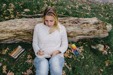 Pretty young woman in white sweater and blue jeans draws in a notebook with colored pencils sitting on the grass and leaned into the trunk of a dry tree