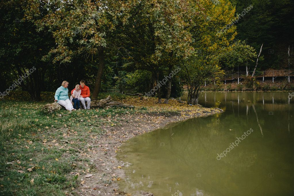 girl, young man in a red sweater and an elderly woman sitting on a log by the lake. daughter, father and grandmother have fun outdoor in the park