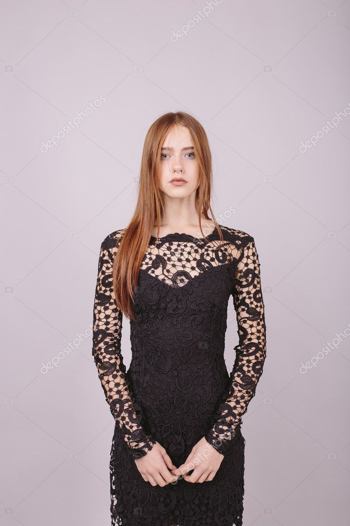 Fashion portrait of a beautiful girl in black lace dress on a gray background. Studio shot. Model test. Empty space for text, copy space