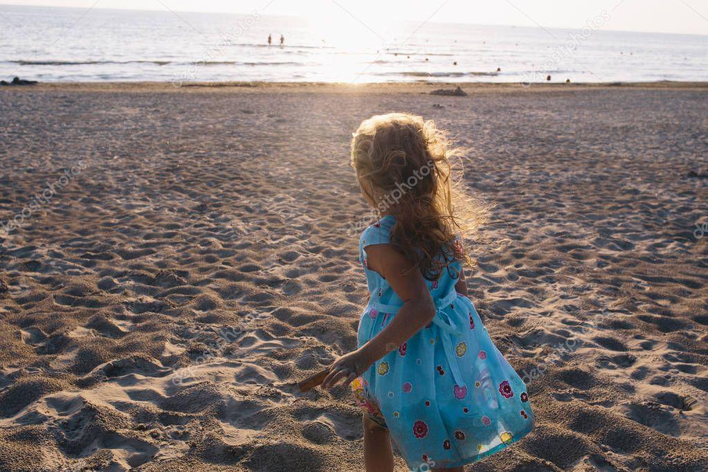 girl in  dress is running on beach