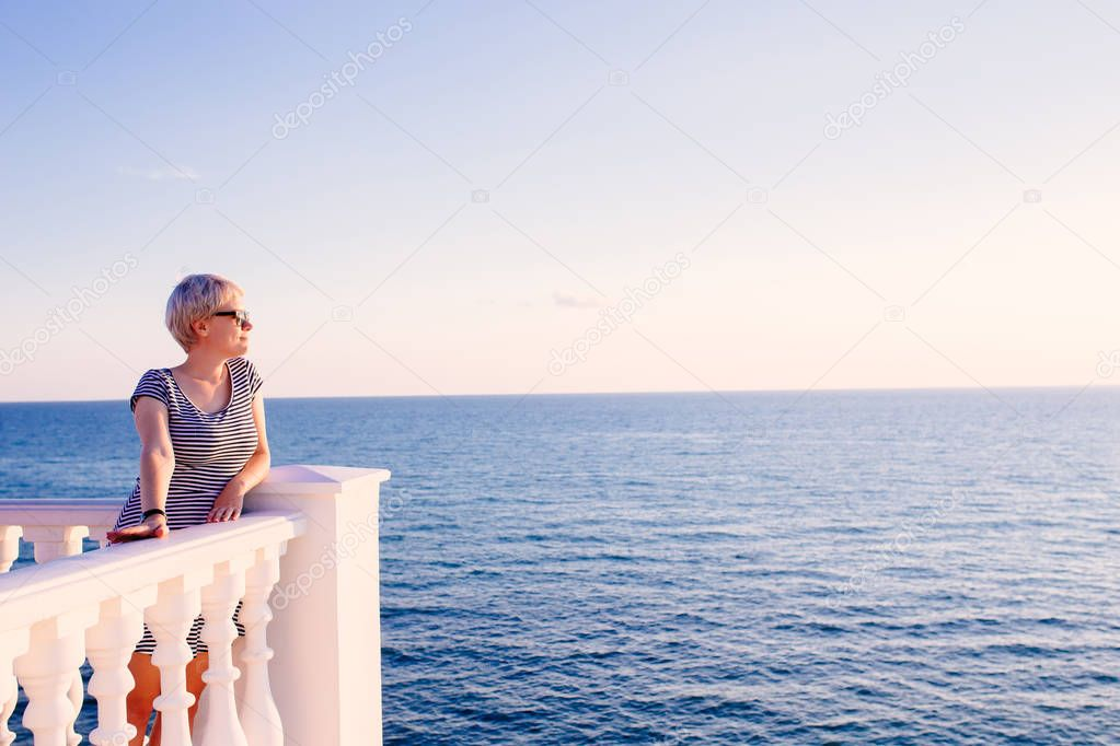 woman on balcony looking at the ocean