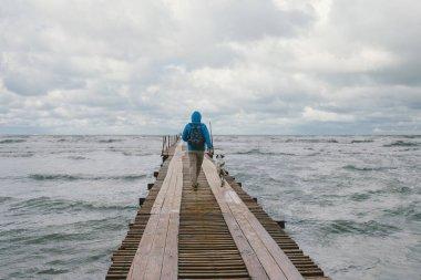 man walking on wooden pier