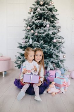 sisters at home with Christmas tree