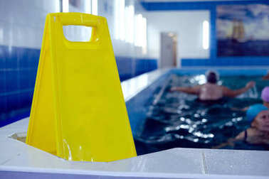 Yellow plastic sign by swimming pool. Copy space. Empty space for text. Pool in nursing home