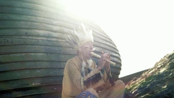 Indián v národním kroji hraje na flétnu v blízkosti lodi na břehu řeky 4k