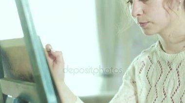 Nő a művész egy festőállvány felhívja a virág mellett egy pillangó ül 4k