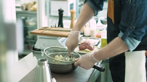 Šéfkuchař restaurace připravuje pokrmy v kuchyni. 4k