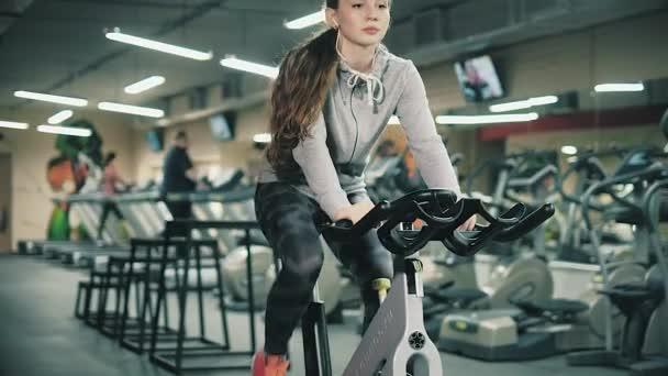 Krásná mladá dívka v tělocvičně, třást nohy na cyklistický trenažér, usmívají se na kameru. Koncept: milovat sport, navštěvovat tělocvičnu, správná výživa, štíhlé tělo, aby se zdravá. 4k
