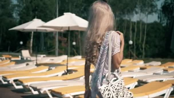 Beautiful woman lying on deck chair Young woman relaxes by the pool,video clip