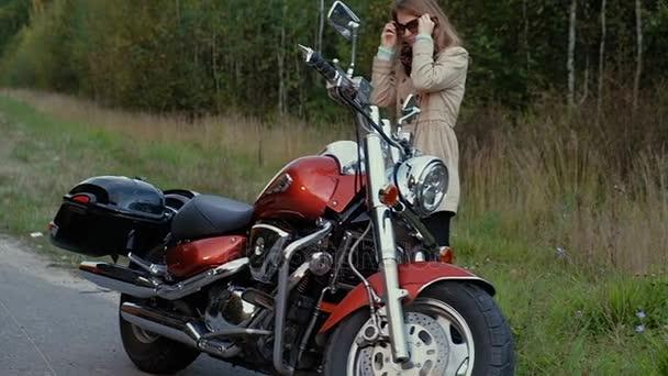 Mladá dívka s hnědými vlasy sedí na motorce v blízkosti silnice.