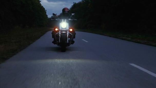 Muž jede na motorce po silnici v lese