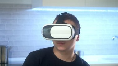 Man Wearing VR Headset at kitchen. Using Gestures with Hands.