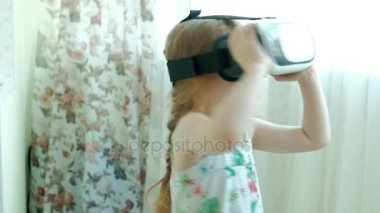 Little girl in white shirt watching 360 video at home, wearing VR headset.