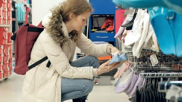 Žena v obchodě boty zvolí boty pokusí