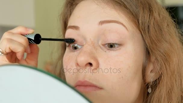 Mladá žena položila na řasenku a hledá v ruce zrcadlo v ložnici doma
