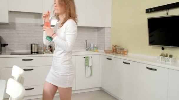 Happy kudrnaté vlasy dívka tančí v kuchyni divoce poskakují vlasy šaty doma divoké baví poslech hudby