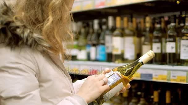 Mladá žena v supermarketu nakoupí víno