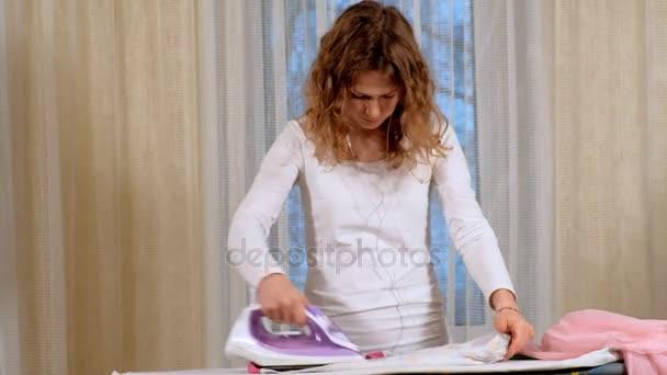 Atraktivní a krásná žena, žehlení prádla v domácnosti