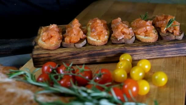 Man preparing Italian bruschetta with baked tomatoes, basil and cheese. Italian food slow motion