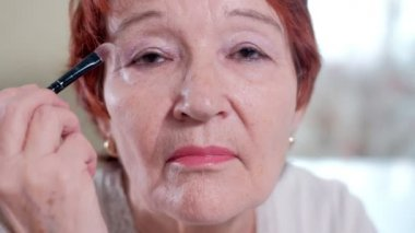 old woman makes a makeup in front of a mirror at home