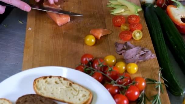 Muži Příprava Italská bruschetta s pečenými rajčaty, bazalkou a sýrem. Italské jídlo Zpomalený pohyb