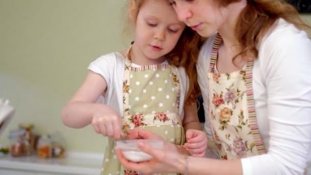 Mladá šťastná matka a její roztomilé kudrnaté batole daughterr v kuchyni vařit