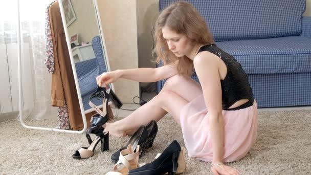 eine Frau probiert Schuhe an, wählt aus mehreren Paaren