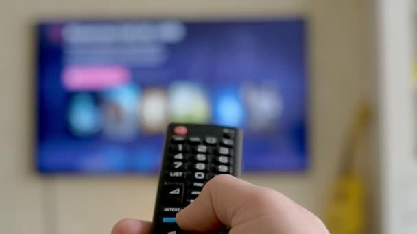 Ruce držte dálkového ovládání televizoru. TV na pozadí.