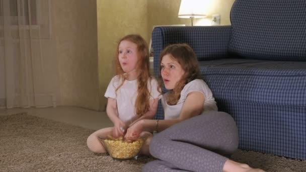 Milující rodina. Matka a její dcera dítě dívka jíst popcorn na podlaze v pokoji. přední části televizoru