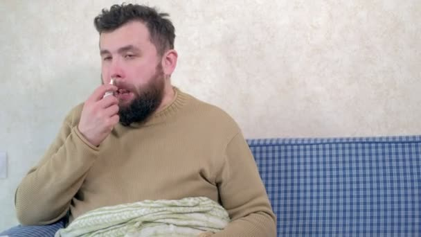 Ein Mann mit einem kalten sitzt auf der Couch. Er streut ein spezielles Nasenspray in die Nase