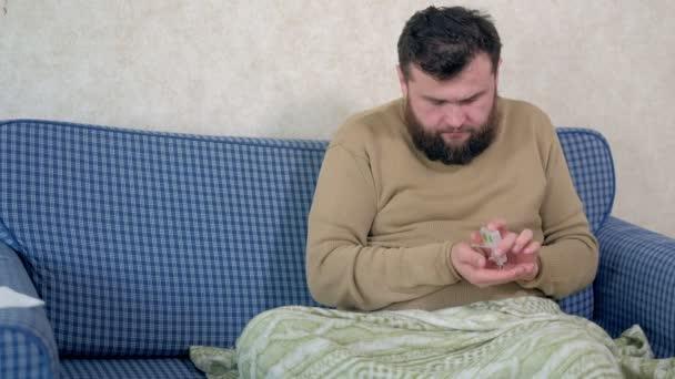 Mann trinkt Wasser mit Tabletten, sitzt im Bett.