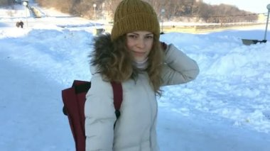 FOLLOW Young female hiking with a backpack in beautiful winter sity,