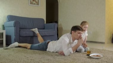 man and daughter watching television, sitting on the floor eating snacks
