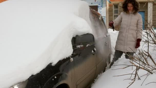 junge Frau säubert Auto nach Schneesturm mit Kratzer