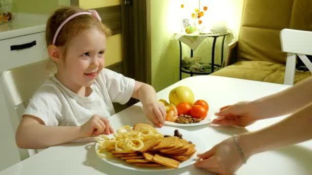 Krásná roztomilá dívka odmítá občerstvení, čokoláda, chipsy, výběr ovoce