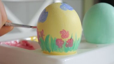 Mother and daughter draw Easter eggs with colored paints