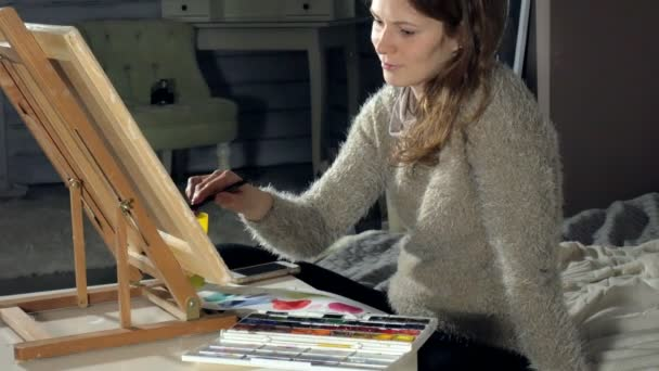 Adult women paint with colored watercolor paints in an art school
