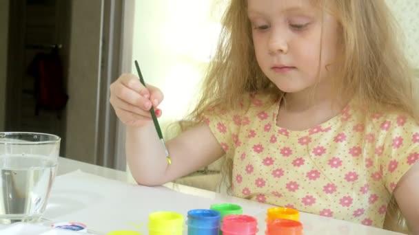 gyönyörű vörös hajú kislány festékek paintand kefével asztalnál ül