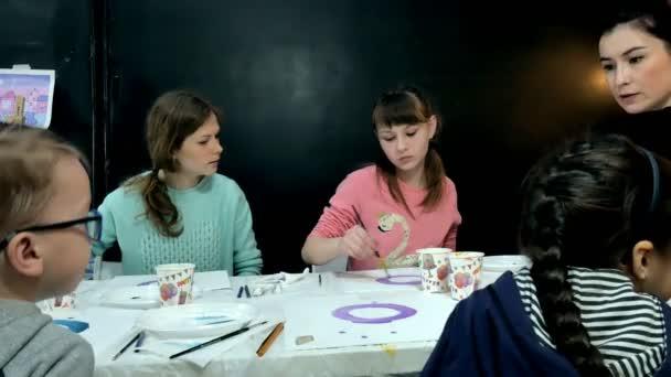 Gyermekek-fiúk és a lányok együtt ül az asztalnál, tantermi és rajz. Velük a fiatal és gyönyörű tanár.