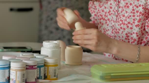 Žena s barevnými laky maluje dřevěné panenky ve svém domácím studiu, Matryoshka malba