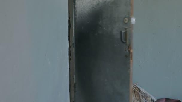 Vojáci v maskování s vojenskými zbraněmi zaklepat ven ze dveří a proveďte převzetí staré budovy, vojenský koncept