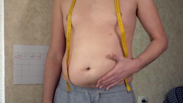 Egy kövér ember intézkedések a dereka, egy nagy sör hasa, az egészséges életmód felveszi kövér redők