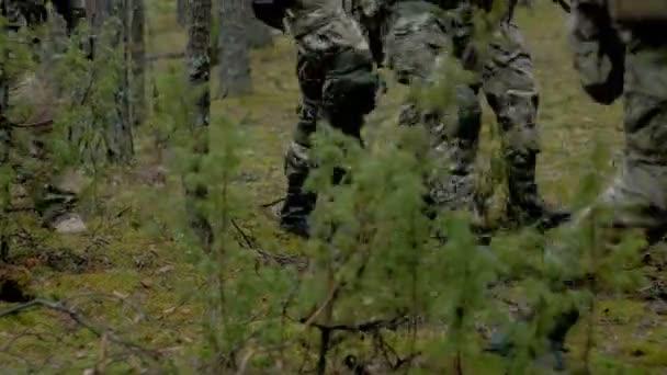 Katonák harci fegyverekkel álcázás az utat az erdőn, azzal a céllal, rögzítése, hogy a katonai koncepció kívüli
