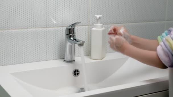 Muž si myje ruce mýdlem v koupelně. Hygiena
