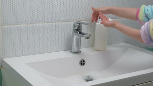 Egy férfi szappannal mossa a kezét a fürdőszobában. Higiénia