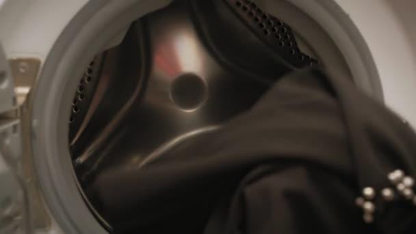 Eine Frau sortiert Wäsche vor dem Waschen.