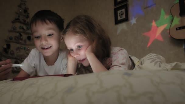 Dítka, bratr a sestra leží na posteli a hrají si před spaním na desce..