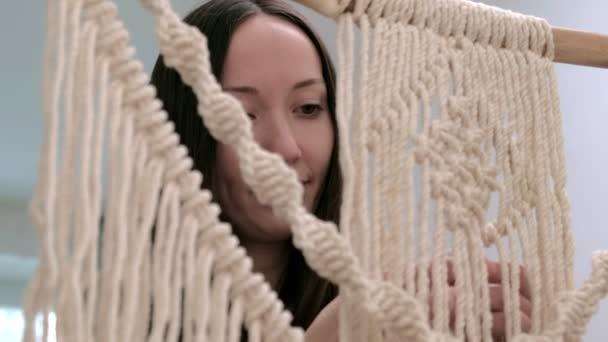 Frau webt Makrama an einem Stock.