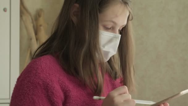 Mädchen in medizinischer Maske studiert während der Coronavirus-Pandemie zu Hause