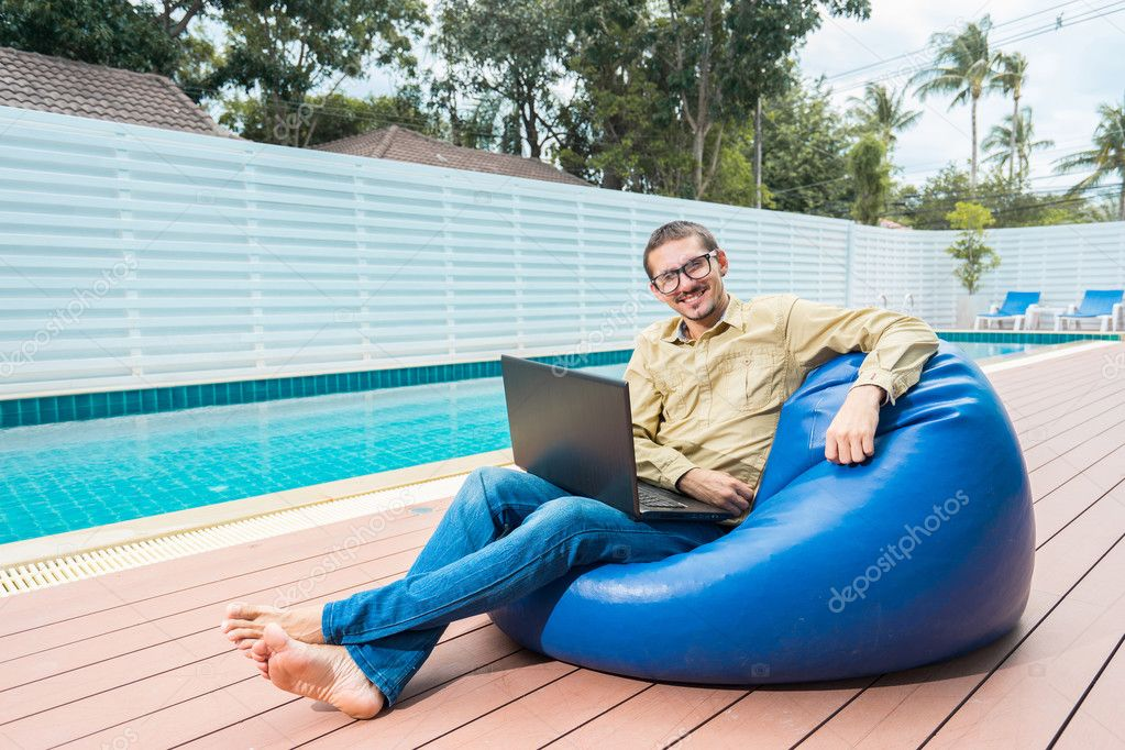 Sit In Pool Zitzak.Man In Glasses Working On Laptop While Sitting On The Beanbag